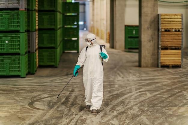 Personne dans une combinaison de protection blanche rafraîchissant et nettoyant un couloir de l'espace intérieur de l'entrepôt lutte contre covid 19, la vie des coronavirus, reste en bonne santé, garde la distance sociale, arrête de propager le virus corona