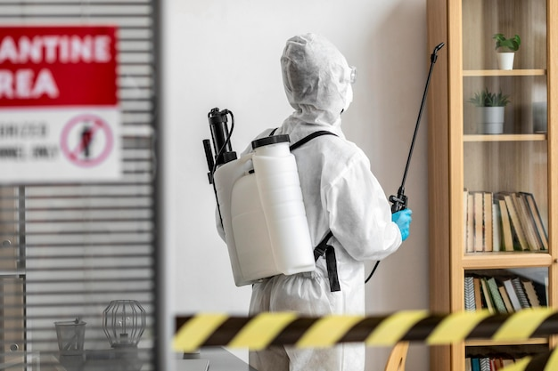Personne dans un équipement spécial désinfectant une zone réglementée