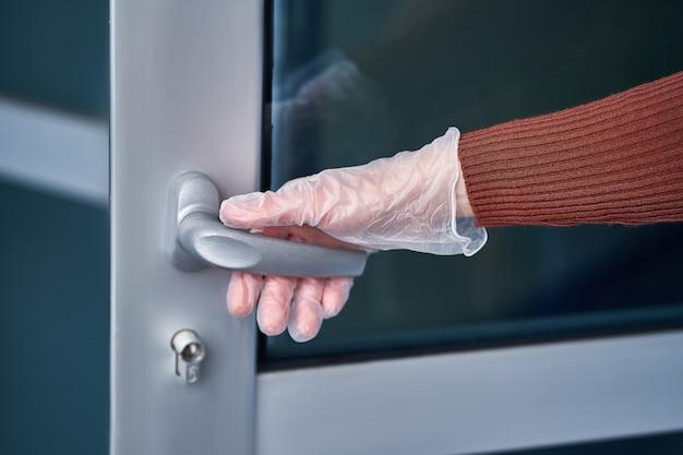 Personne dans des gants de protection en caoutchouc transparent tenant la poignée de porte pendant une épidémie de virus de la grippe, une épidémie de coronavirus et des maladies infectieuses
