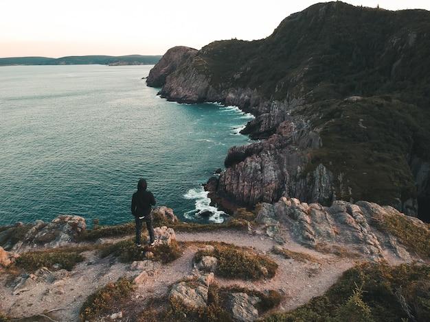 Personne debout sur la falaise pendant la journée