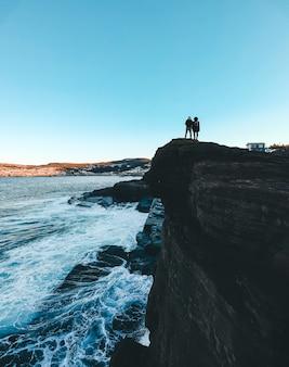 Personne debout sur une formation rocheuse près de la mer pendant la journée