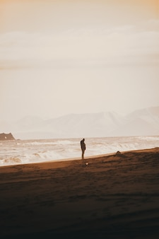 Personne debout sur la plage de sable avec un ciel blanc clair