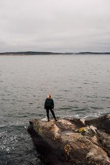 Personne debout sur un rocher au bord de la mer à la recherche d'un côté