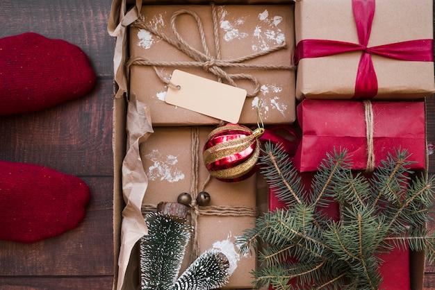 Personne debout sur le sol avec des boîtes-cadeaux dans une boîte en carton