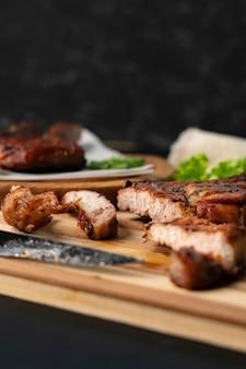 Personne découpant un steak de bœuf cuit ou grillé au couteau sur une planche de bois