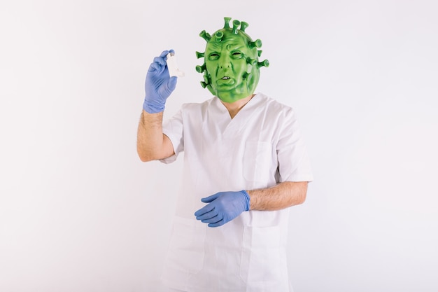 Personne déguisée en coronavirus avec un masque en latex virus covid19, vêtue d'un costume de médecin, prenant un inhalateur d'asthme, sur fond blanc.
