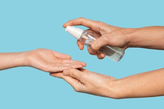 Personne désinfectant les mains isolé sur bleu