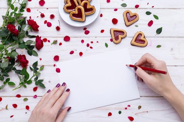 Personne dessin sur un papier blanc avec un crayon rouge près de cookies en forme de coeur avec des pétales de rose