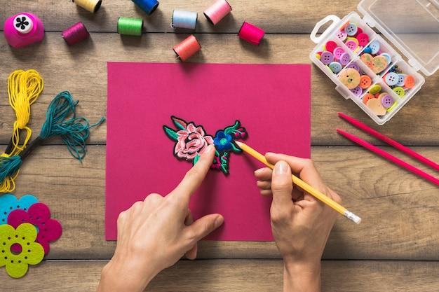 Une personne dessinant le contour du patch sur du papier rose