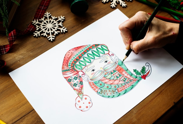 Une personne dessinant un visage coloré du père noël