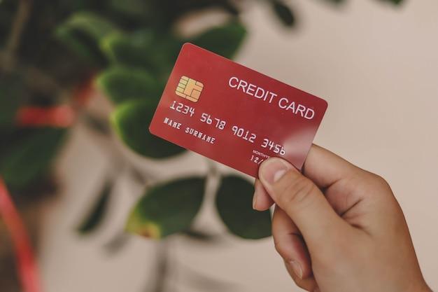 La personne détient une carte de crédit, une carte de crédit peut être utilisée pour payer des biens et services dans des magasins de détail, des restaurants ou des achats en ligne. concept d'utilisation d'une carte de crédit.