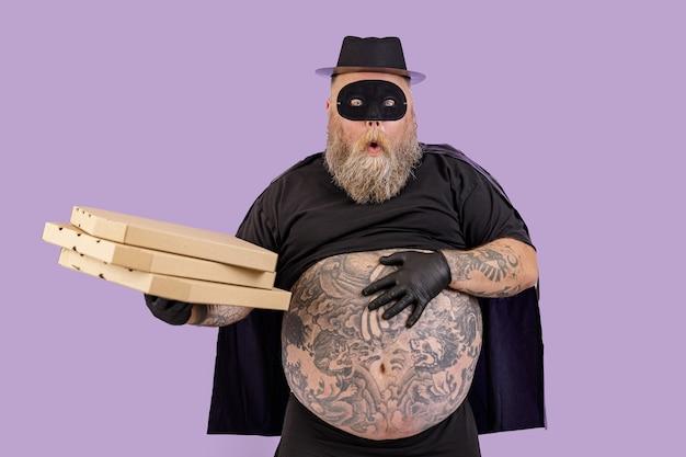 Une personne dodue surprise en costume de zorro tient des boîtes de pizza sur fond violet