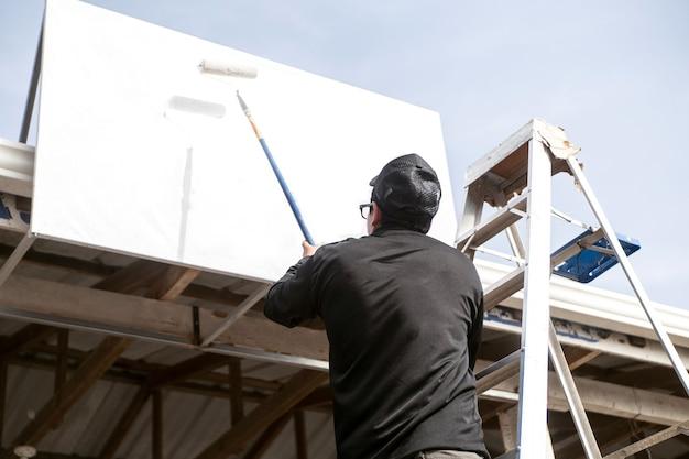 Une personne sur une échelle peignant un panneau blanc ou une bannière. copiez l'espace et simulez.