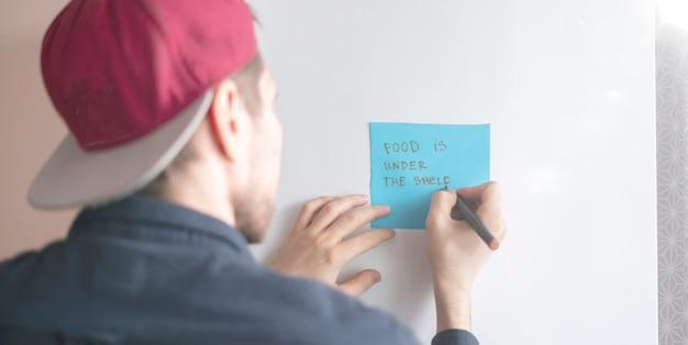 Une personne écrit un texte de rappel sur l'autocollant de note sur le réfrigérateur
