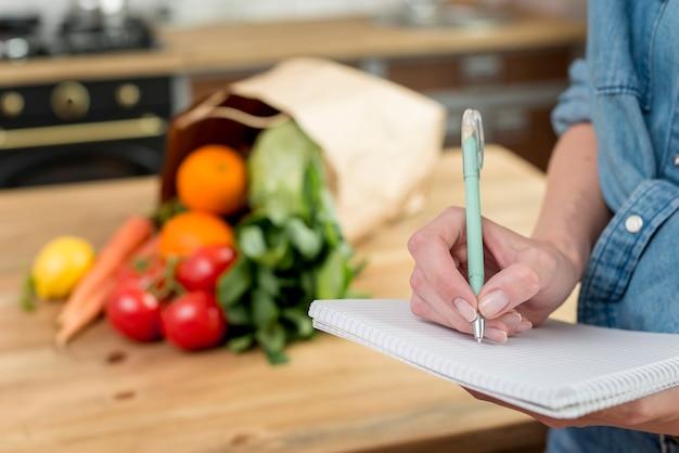 Personne écrivant une recette dans le cahier