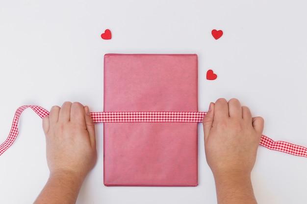 Personne, emballage rose, boîte cadeau, sur, table