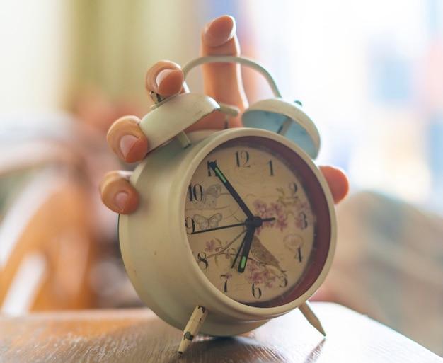 Une personne endormie épuisée éteint le réveil blanc au matin b