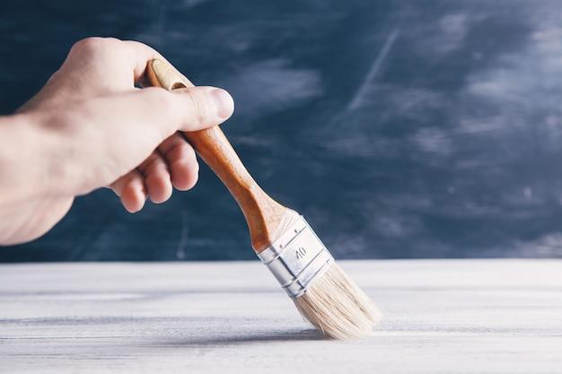 Personne enlève la poussière de la table avec une brosse