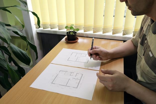 La personne est assise à table près de la fenêtre et prend des notes dans le plan d'étage architectural de la petite maison