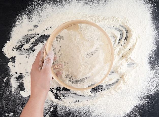 Personne est titulaire d'un tamis en bois rond et tamiser la farine de blé blanc