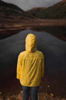 Une personne face à la caméra avec un sweat à capuche ciré jaune regardant une rivière rouge en espagne.