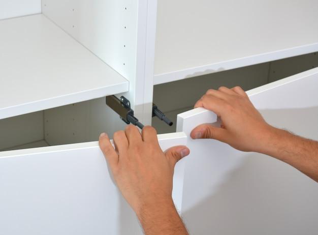 Personne faisant une armoire en bois blanc avec des vis