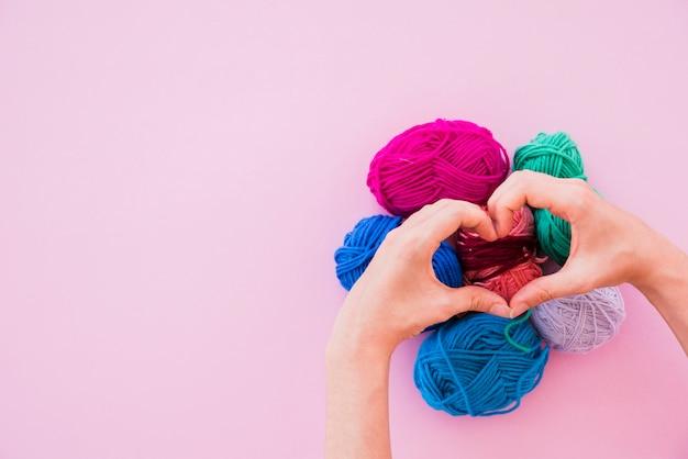 Une personne faisant le coeur sur les boules de laine colorées sur fond rose