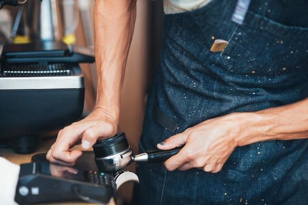 Personne faisant du café frais par machine à caroube