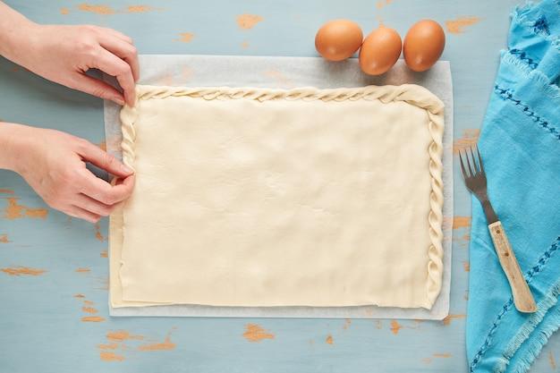 Personne fait un bord à la pâte de l'empanada crue galicienne remplie de thon