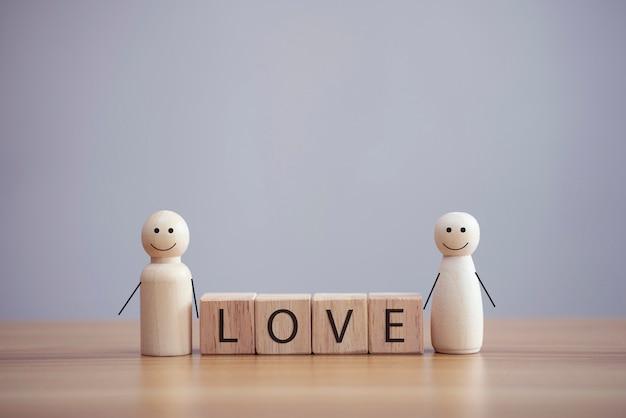 Une personne de famille en bois heureuse modèle un smiley avec un mot amour sur fond de table de cube en bois