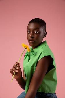 Personne fluide de genre africain posant dans une chemise verte