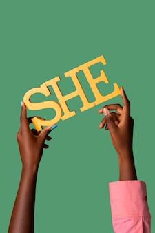 Personne fluide de genre tenant un pronom féminin sur papier