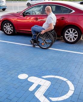 Personne handicapée physique montant dans une voiture rouge depuis un fauteuil roulant