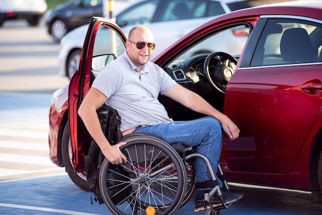 Personne handicapée physique montant dans une voiture rouge en fauteuil roulant