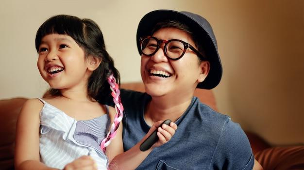 Personne heureuse, une jolie fille souriante assise sur un canapé avec son parent.