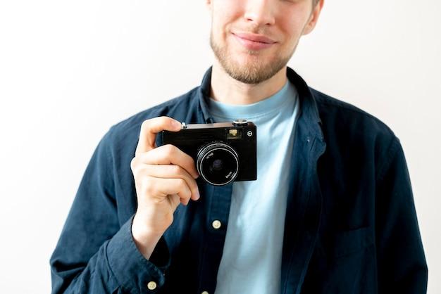 Une personne heureuse tenant un vieil appareil photo vintage et faisant des photos