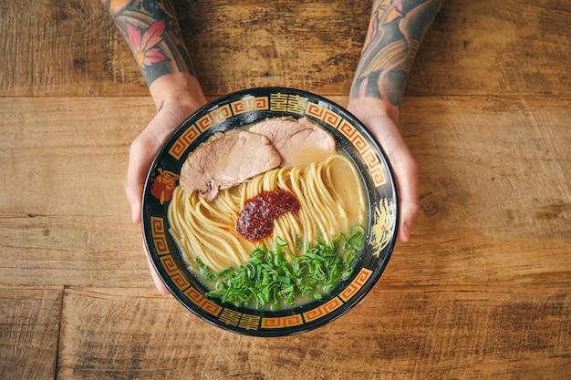 Personne hipster sans visage avec une délicieuse soupe de nouilles japonaises