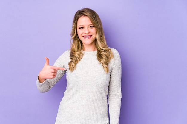 Personne de jeune femme caucasienne pointant à la main vers un espace de copie de chemise, fier et confiant