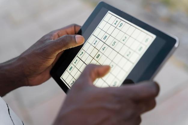 Personne jouant au sudoku sur une tablette