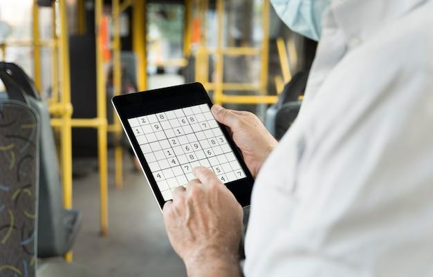 Personne jouant à un jeu de sudoku sur une tablette