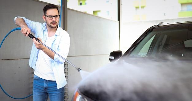 Personne lavant sa voiture dans un jet de lave-auto avec un nettoyant industriel