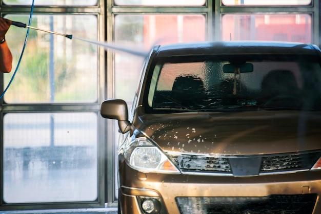 Personne lavant sa voiture dans une station avec un nettoyeur spécial, services de lavage de voiture