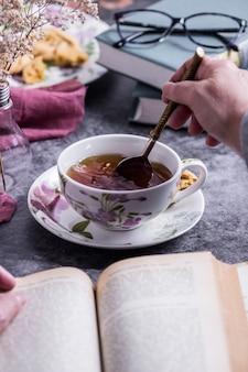 Une personne lisant un livre en remuant le thé blanc