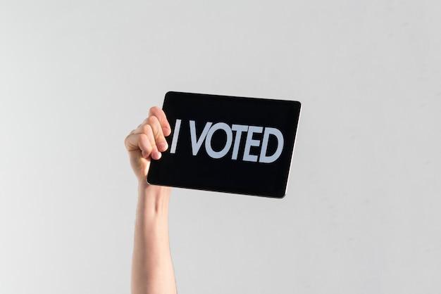 Une personne avec une main levée avec plaque noire et texte j'ai voté pour l'élection démocratique