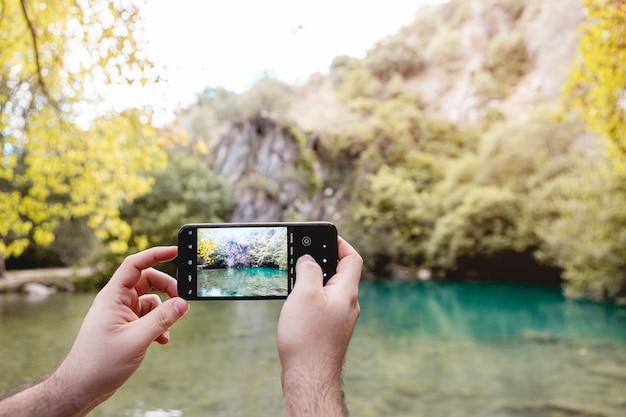Personne mains prenant une photo du lac avec un téléphone portable