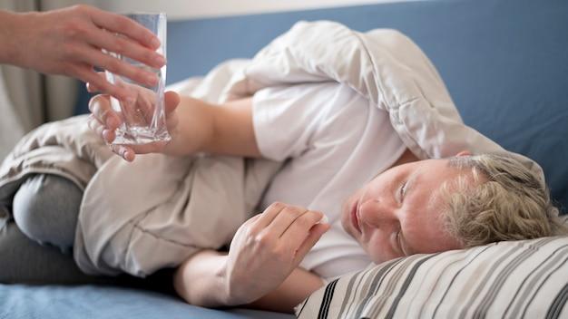 Personne malade recevant un verre d'eau