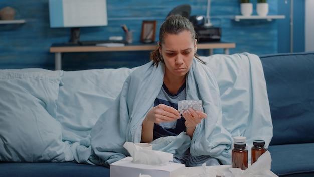Personne malade regardant des comprimés de capsule et une bouteille de pilules