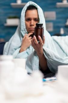 Personne malade tenant une bouteille de capsules