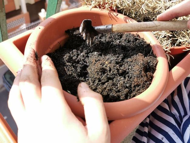 Personne manipulant le sol dans un pot pour planter des fleurs