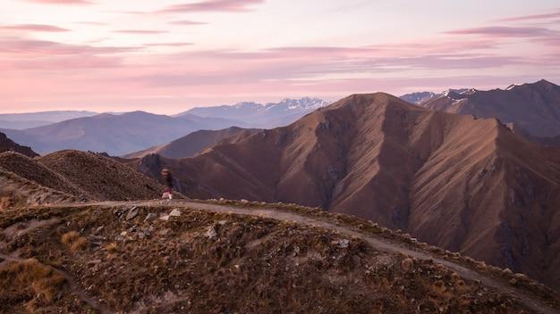 Personne marchant sur le sentier de montagne pendant le lever du soleil tourné sur roys peak wanaka nouvelle-zélande